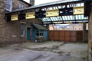 This area was the terminus for the railway. Weighing office on the left behind which was the upholsterer's shop, above the upholsterer's was the male clothing shop, behind the camera both upstairs and down was the bakehouse. On the right under the glass roof is the back door to the general stores. The black and yellow beams are part of the gantry used to hoist supplies from the train. It is believed that the rails of the old railway line are still in situ covered by asphalt.